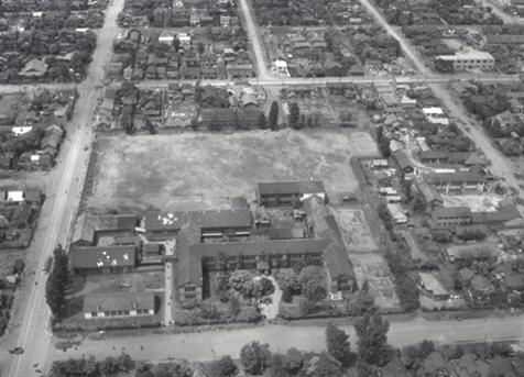 かつて1962年(昭和37)まで北4条西19丁目にあった札幌西高等学校を南から北に向かっての空撮(1957年(昭和33)当時)。現在、西本願寺札幌別院と札幌龍谷学園高校のある場所です。校舎敷地北側の北5条通りと西側の20丁目(市場通り)に市電北5条線が走っているのが見えます。右端の中心あたりに現在のミニ大通17丁目の突端もわずかに見えます。札幌市公文書館所蔵写真