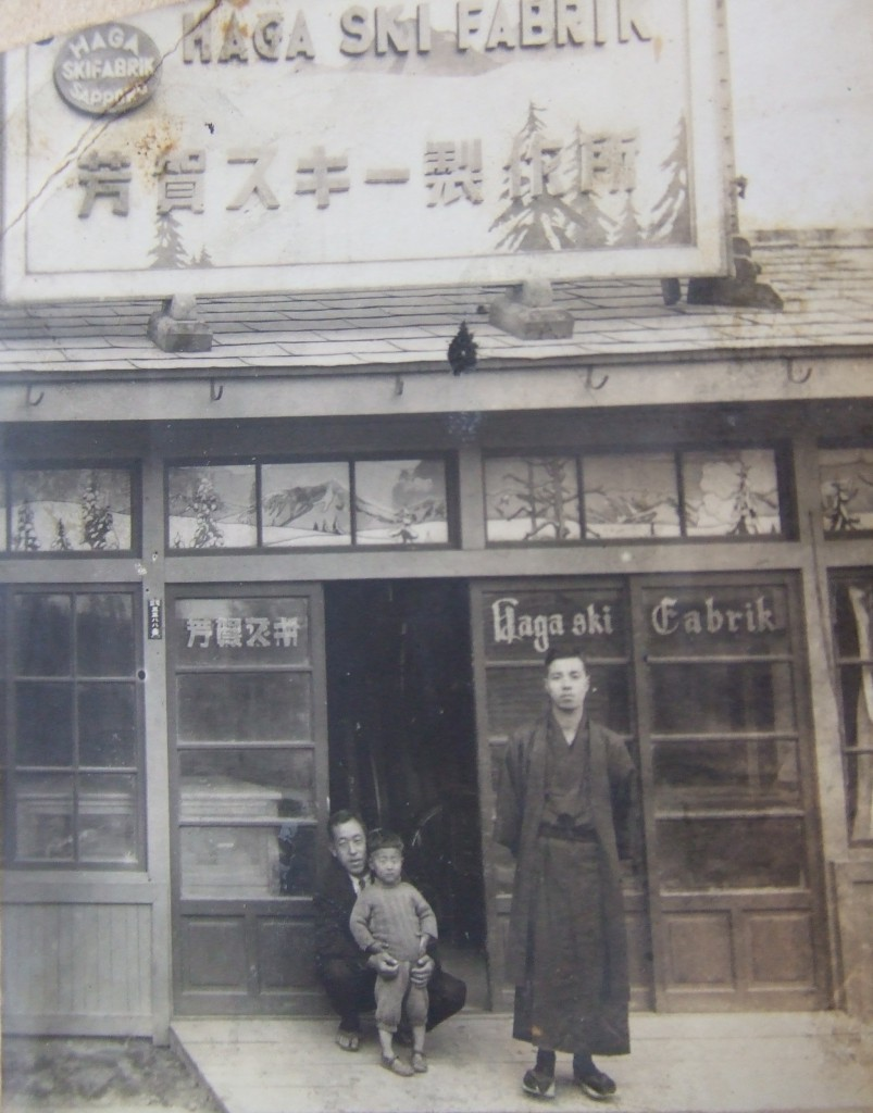1937年(昭和12)北5条西19丁目にあった芳賀スキー店舗前での写真(芳賀孝郎さん提供) 当時3才の芳賀さんを抱えておられるのが、芳賀スキー製作所社長であられたお父様の芳賀藤左衛門さんです。